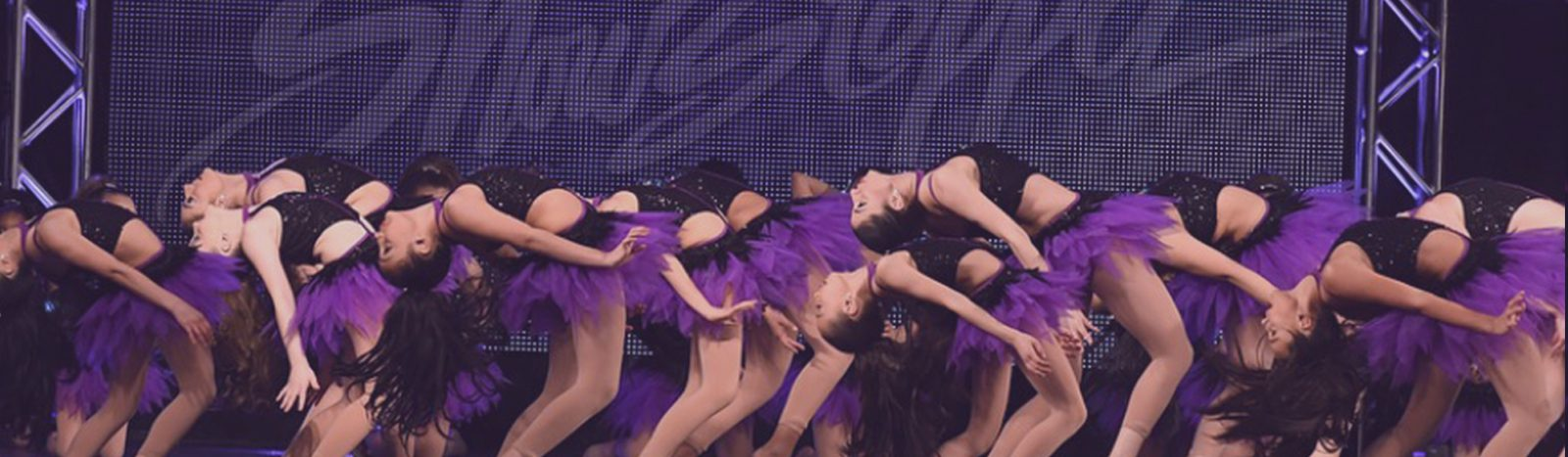 girls in purple dancing on stage at showstopper dance competition